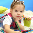 Cute little girl playing with multicolor pencils, on blue background — ストック写真 #17992317