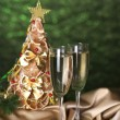 Beautiful christmas tree and  glasses of champagne on  shine green background - Stock Photo
