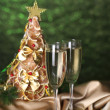 Beautiful christmas tree and  glasses of champagne on  shine green background - Стоковая фотография