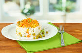Risotto on plate on wooden table on bright background — Stock Photo