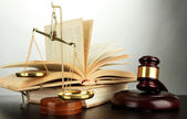 Golden scales of justice, gavel and books on grey background — Photo