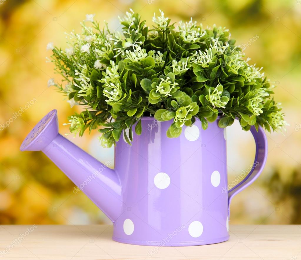 Decorative flowers in watering can on bright background — Stock Photo #17992065