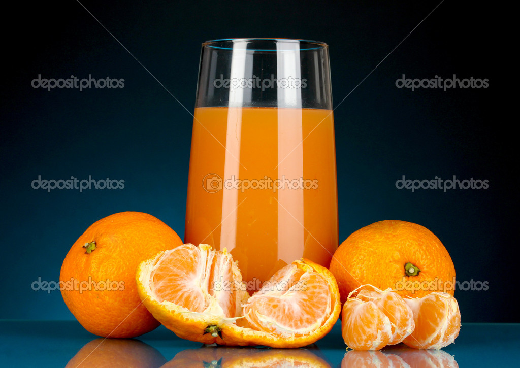Delicious tangerine juice in glass and mandarins next to it on dark blue background — Stock Photo #17992223