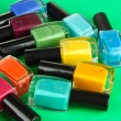 Group of bright nail polishes, on green background — Stock Photo #18037237