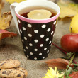 Cup of hot tea and autumn leaves, on burlap background — Stock Photo