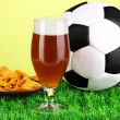 Stock Photo: Glass of beer with soccer ball on grass on green background