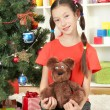 Little girl holding toy near christmas tree — Stockfoto