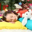 Little girl sleeping near christmas tree — Stok fotoğraf
