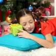 Foto Stock: Little girl sleeping near christmas tree