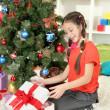 Little girl with present box near christmas tree — Stock Photo