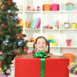 Little girl with large gift box near christmas tree — ストック写真