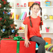 Little girl with large gift box near christmas tree — Stock Photo #18038479