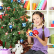 Foto Stock: Little girl decorating christmas tree