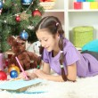 Little girl writing letter to Santa near christmas tree — Stock Photo #18038507