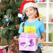 Little girl holding gift boxes near christmas tree — Stock Photo #18038559