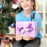 Little girl holding gift box near christmas tree — Stock Photo