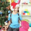 Little girl with present box near christmas tree — Stock Photo #18038577