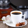 White cup of Turkish coffee with coffee maker and coffee mill on wooden table — Stock Photo