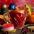 Fragrant mulled wine in glass with spices and oranges around on wooden table on red background — Stockfoto