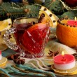 Fragrant mulled wine in glass with spices and oranges around on wooden table — Stockfoto