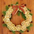Christmas wreath of dried lemons with fir tree and bow, on wooden background — Photo