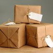 Parcels boxes with kraft paper, on wooden table on grey background — Stock Photo #18039657