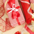 Stock Photo: Rolls of Christmas wrapping paper with ribbons, bows on wooden background