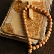 Bible, rosary and cross on wooden table close-up — Stockfoto