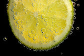 Slice of lime in the water with bubbles, on black background — Stock Photo