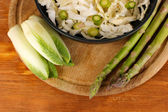 Pan with coleslaw, asparagus and chicory on wooden table background — Stock Photo