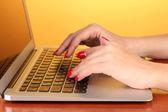 Dettaglio delle mani femminile utilizzando computer sul colore di sfondo — Foto Stock