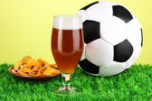 Glass of beer with soccer ball on grass on green background — Stock Photo