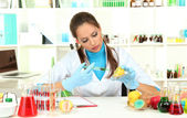Young female scientist injecting GMO into lemon in laboratory — Stockfoto