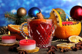 Fragrant mulled wine in glass with spices and oranges around on wooden table on blue background — Стоковое фото