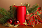 Two candles and christmas decorations, on brown background — Stock Photo
