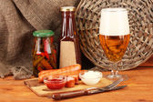 Bira ve ahşap masa üstünde çul arka plan üzerinde ızgara sosis — Stok fotoğraf
