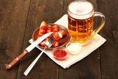 Beer and grilled sausages on wooden background — Stock Photo