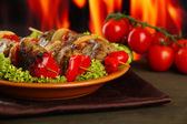 Tasty grilled meat and vegetables on plate, on fire background — Stock Photo