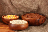 Raw corn,buckwheat and wheat in wooden bowls on table on sackcloth background — Zdjęcie stockowe