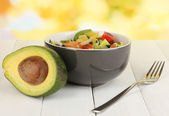Tasty avocado salad in bowl on wooden table on natural background — Stock Photo