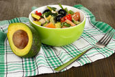 Tasty avocado salad in bowl on wooden table close-up — Stock Photo