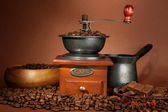 Coffee grinder, turk and coffee beans on brown background — Stock Photo