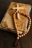 Bible, rosary and cross on wooden table close-up — Foto Stock