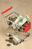 Money in cart on wooden table close-up — Stock Photo