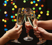 Woman hand with glasses of champagne, on garland background — Stock Photo