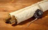 Old scroll, on wooden background — Stock Photo