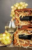 Dřevěné pouzdro s lahví vína, sklenice na víno a hroznovou na dřevěný stůl na šedém pozadí — Stock fotografie