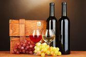 Kahverengi zemin üzerine ahşap masa üstünde şarap şişeleri ile ahşap kasalar — Stok fotoğraf