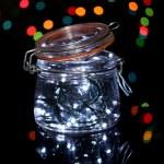 Christmas lights in glass bottle on blur lights background — Stock Photo #18040243