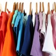 Choice of clothes of different colors on wooden hangers, isolated on white — Stock Photo #18040257